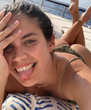 Sara Sampaio poking her tongue lying prone in a bikini