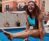 Dora Madison Burge poking her tongue out in a front knot tied T-shirt and panties with her legs raised balanced on pool handrails