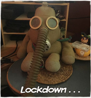 "A photo of a stuffed monkey in a large gasmask on a wicker coaster on the edge of a desk, with the caption ""Lockdown…"""